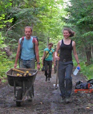 volunteers carrying tools to work site