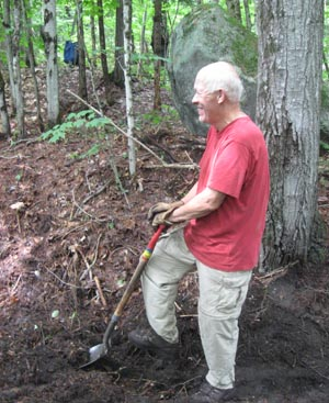 volunteer digs drainage ditch